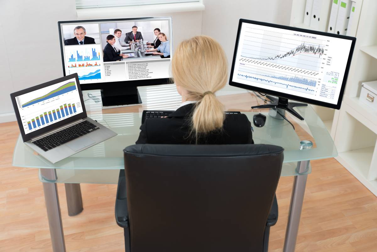 Woman sitting at a desk with three monitors, collaborating with coworkers via video conference