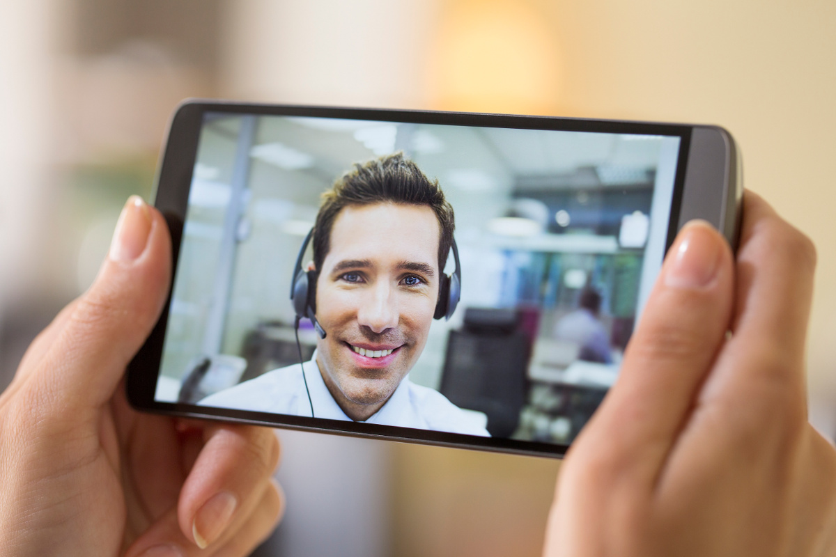 Woman's Hands Holding Cell Phone on Video Call with Smiling Male Customer Service Representative Wearing Headset
